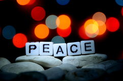 PEACE word. On top of rock formation with bokeh light background Stock Image