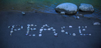 `Peace` word written with pebbles on the sand. Royalty Free Stock Photo