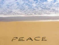 Peace written in golden sand with surf stock photo