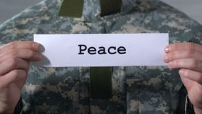 Peace written on paper in hands of male soldier, end of war, reconciliation. Stock footage stock video footage