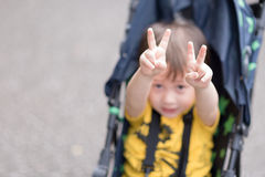Peace. A young boy sitting in a stroller making peace signs with both hands Stock Photo