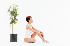 Peaceful african american woman sitting near small tree in pot Royalty Free Stock Photo