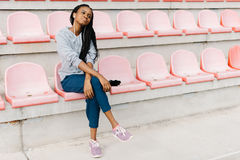 Peaceful afro-american teenager is listening to music in earphones while sitting on the pink seats on the stadium. Peaceful afro-american teenager is listening Stock Image