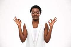 Peaceful attractive african american young woman meditating and keeping calm Royalty Free Stock Image