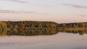 Peaceful autumn nature reflected in calm clear water, river or lake at sunset. Stock footage stock video footage