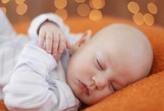 Peaceful baby boy  lying on a bed while sleeping Royalty Free Stock Photography