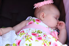 Peaceful baby in dress and hat lying in black baby stroller Royalty Free Stock Photography