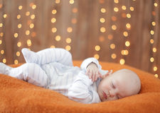 Peaceful baby lying on a bed Stock Images
