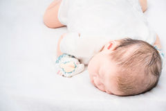 Peaceful baby lying on a bed while sleeping. Royalty Free Stock Photos
