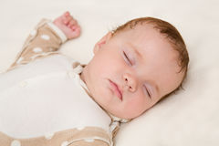 Peaceful baby lying on a bed while sleeping Stock Image