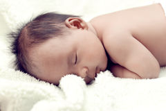 Peaceful baby lying on a bed while sleeping in a bright room Royalty Free Stock Images