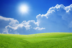 Peaceful background. Peaceful landscape - green grass field, bright sun, blue sky, white clouds - heaven on earth royalty free stock photos