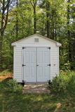 Peaceful backyard scene with small shed tucked in corner of landscaped yard. Peaceful scene with woodsy backyard and small well-kept shed tucked into corner Royalty Free Stock Photos