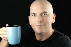 Peaceful bald man lifts mug to camera Royalty Free Stock Photo
