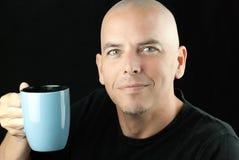 Peaceful bald man lifts mug to camera Royalty Free Stock Photo