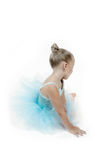 Peaceful Ballerina Child. Ballerina girl sits on the floor and looks back behind her. Blue tutu. With slight desaturation to subdue the colors royalty free stock image