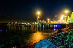 Peaceful Bay Night Scenery. Epic and poetic scenery of a bay in the night with building and dock lights reflecting from the surface of the sea Royalty Free Stock Photos
