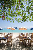 Peaceful beach. Group of chairs and umbrella along the clear beach royalty free stock photography
