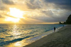 Peaceful beach walk on the sunset after tropical storm when shin sun rays opening the dark dramatic cloudy sky royalty free stock photos