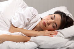 Peaceful beautiful oriental girl sleeping in bed Royalty Free Stock Photography