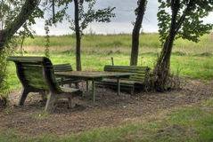 Peaceful Bench. A bench with a table peacefully between some trees Royalty Free Stock Images