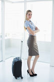 Peaceful blonde businesswoman posing standing next to her suitcase Stock Images