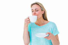 Peaceful blonde drinking hot beverage with eyes closed Royalty Free Stock Image