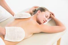Peaceful blonde enjoying an exfoliating back massage Royalty Free Stock Photography