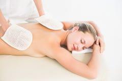 Peaceful blonde enjoying an exfoliating back massage Royalty Free Stock Images