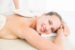 Peaceful blonde enjoying an exfoliating back massage Stock Photos