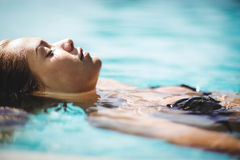 Peaceful blonde floating in the pool Royalty Free Stock Photography