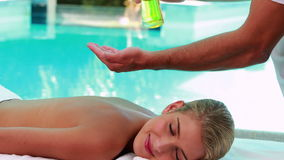 Peaceful blonde getting a massage poolside stock footage
