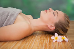 Peaceful blonde lying on bamboo mat with flowers Royalty Free Stock Photography