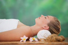 Peaceful blonde lying on bamboo mat with flowers Stock Photo