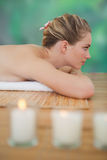 Peaceful blonde lying on bamboo mat Stock Photos