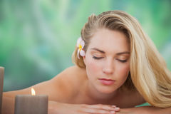 Peaceful blonde lying on towel with candle Stock Image