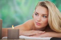 Peaceful blonde lying on towel with candle Royalty Free Stock Photography