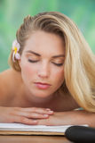 Peaceful blonde lying on towel with candle Royalty Free Stock Photo
