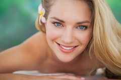 Peaceful blonde lying on towel smiling at camera Stock Images