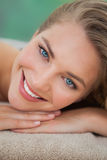 Peaceful blonde lying on towel smiling at camera Stock Image