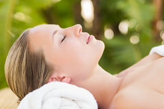 Peaceful blonde lying on towel smiling at camera Stock Photography