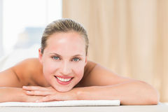 Peaceful blonde lying on towel smiling at camera Royalty Free Stock Photo