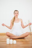 Peaceful blonde sitting in lotus pose on bamboo mat Royalty Free Stock Photos