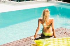 Peaceful blonde sitting on pools edge Stock Photo