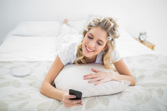 Peaceful blonde wearing hair curlers texting while lying on bed Stock Images