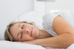 Peaceful blonde woman sleeping in bed Stock Photography