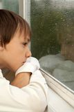 Peaceful boy sitting  at home. Interesting little boy sitting in a room at home Stock Photos