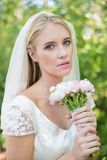 Peaceful bride holding her bouquet wearing a veil looking at camera Royalty Free Stock Images