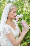 Peaceful bride smelling her bouquet Stock Images