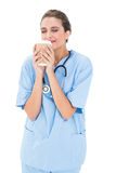 Peaceful brown haired nurse in blue scrubs enjoying coffee smell Stock Photography